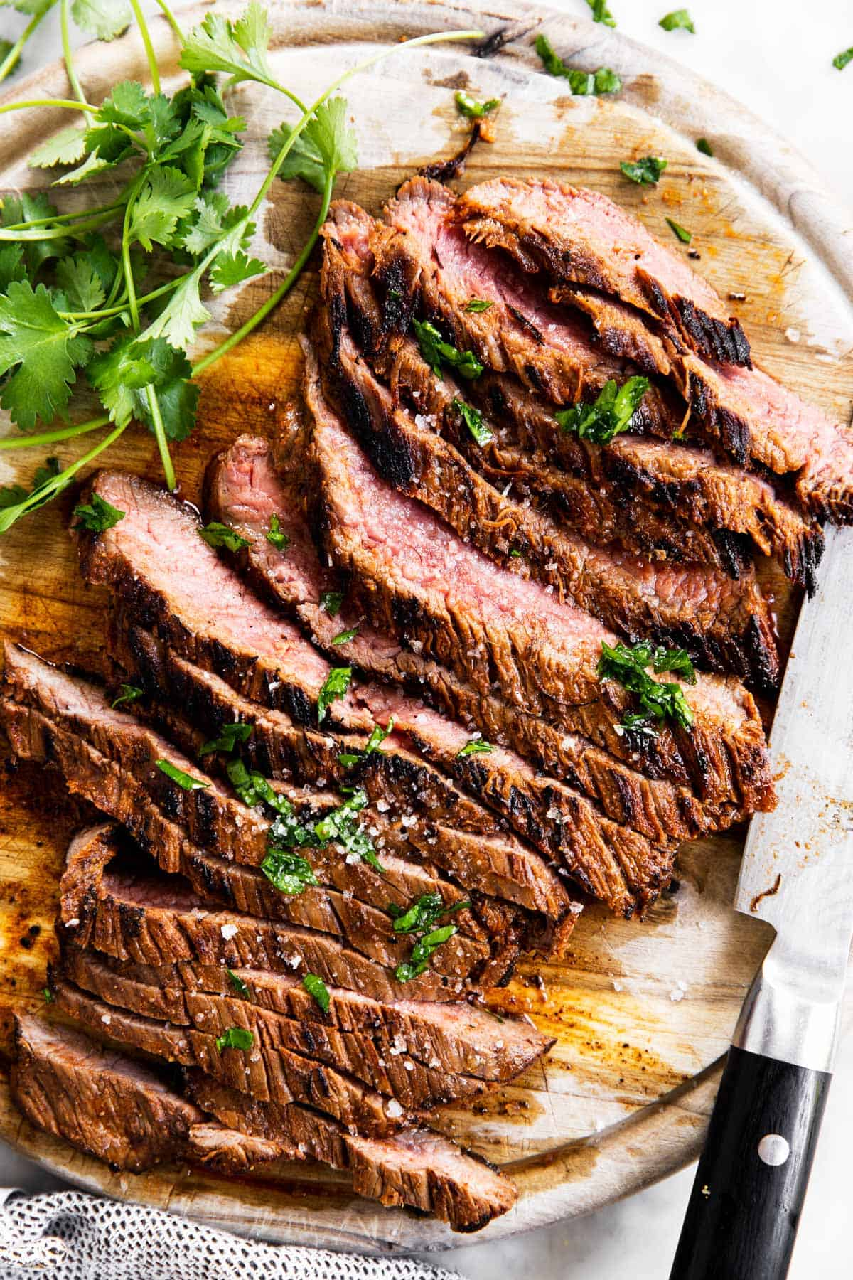sliced flank steak on wooden board with fresh cilantro