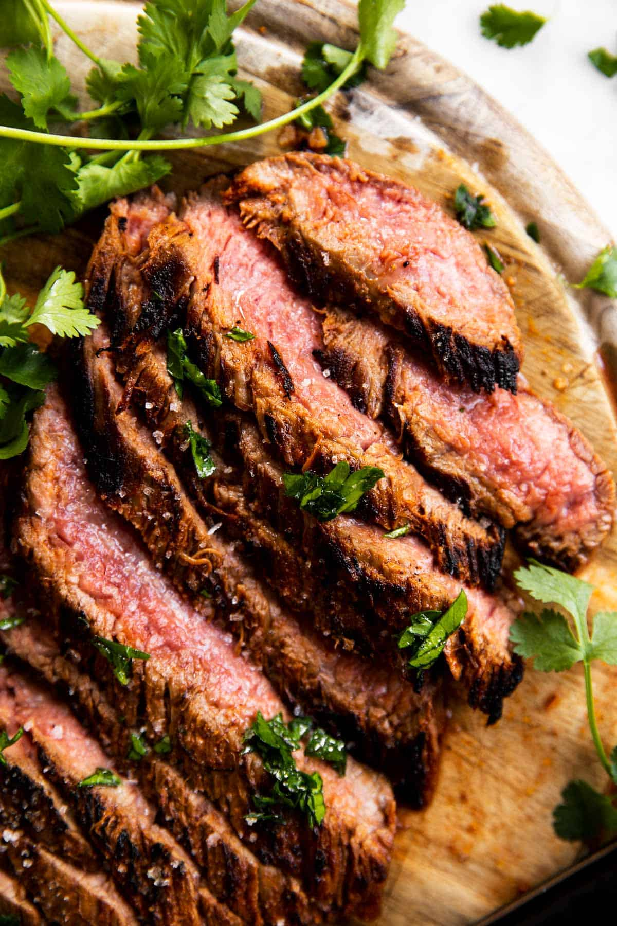 close up photo of sliced flank steak on wooden board with fresh herbs