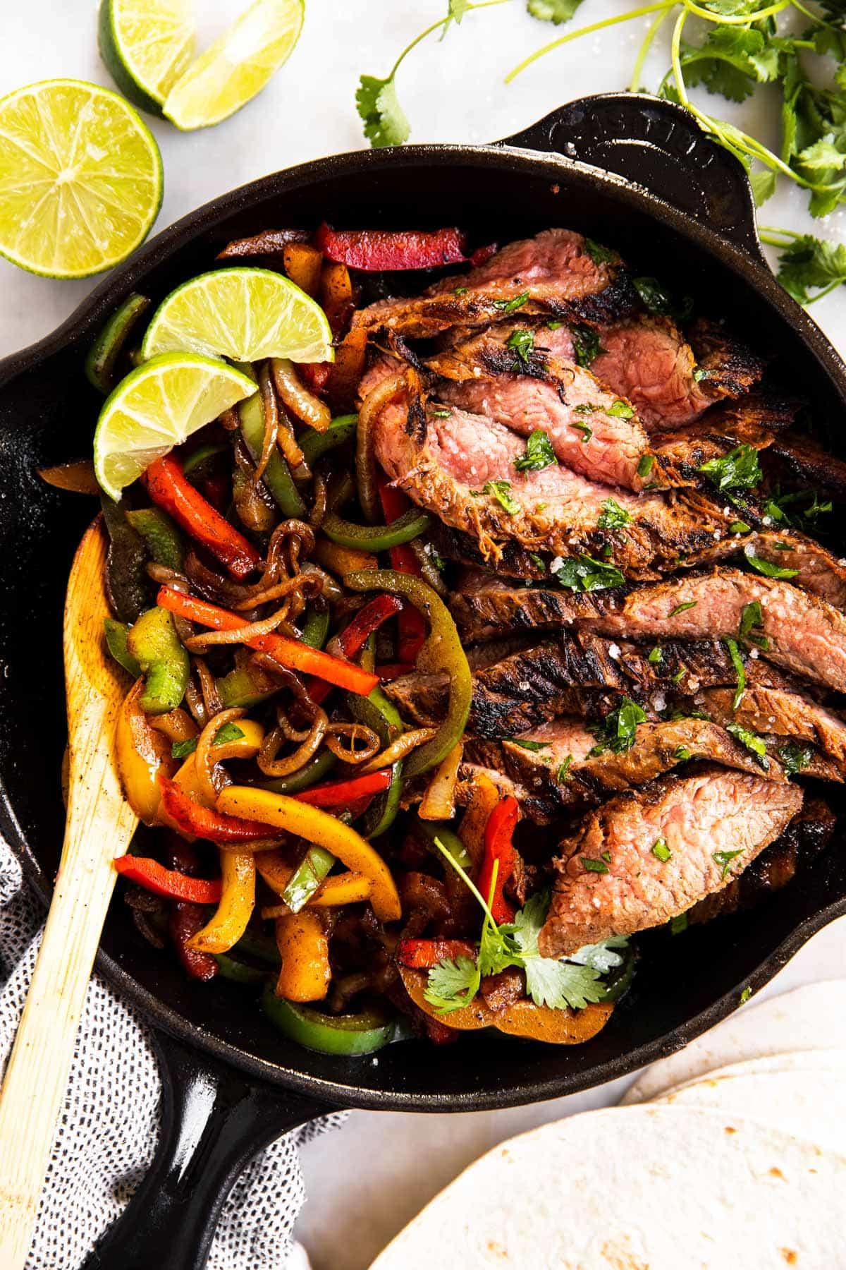 black cast iron skillet with steak fajita filling