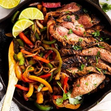 black cast iron skillet with steak fajita filling
