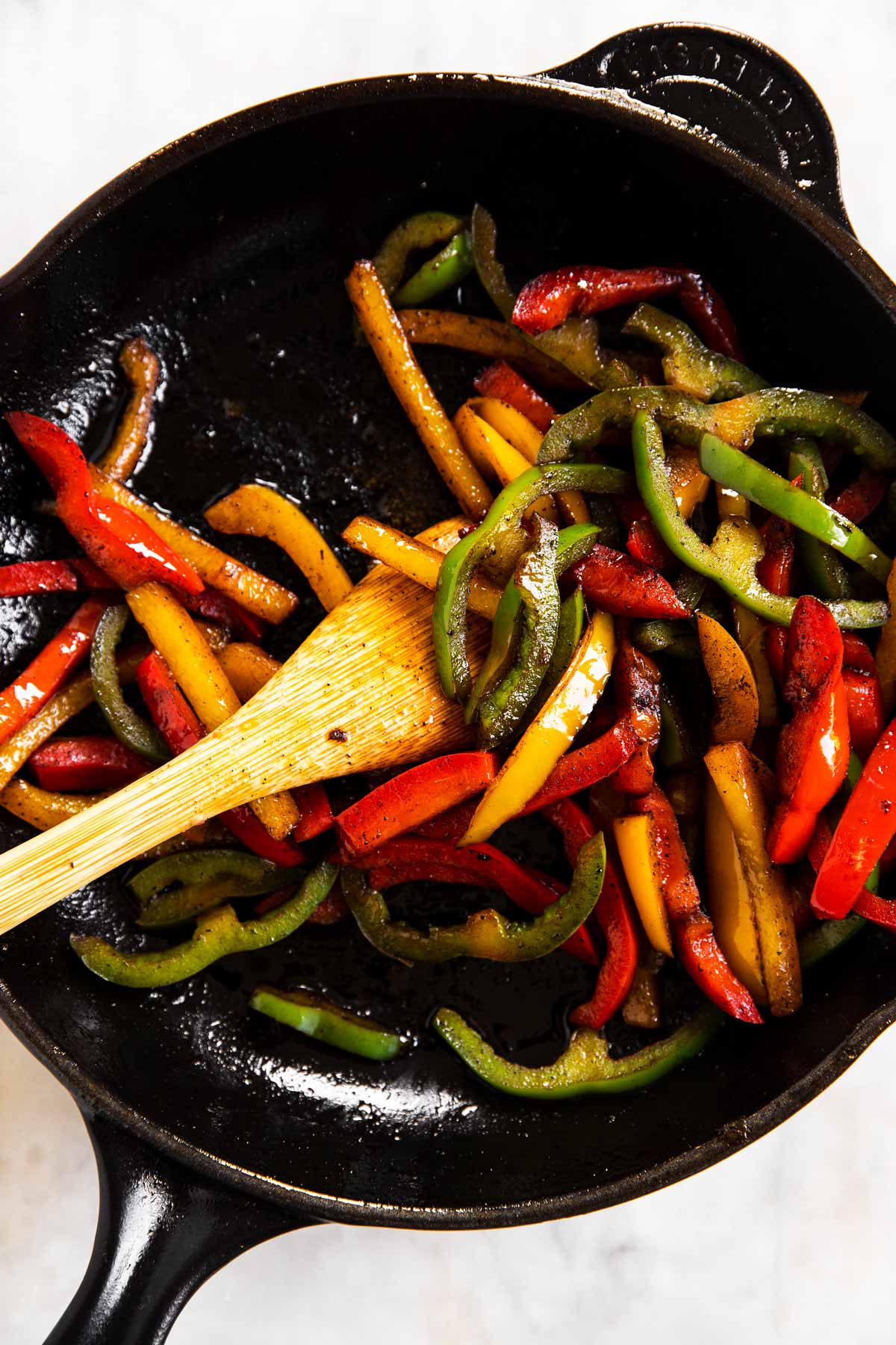 cooked bell peppers in black cast iron skillet with wooden spoon