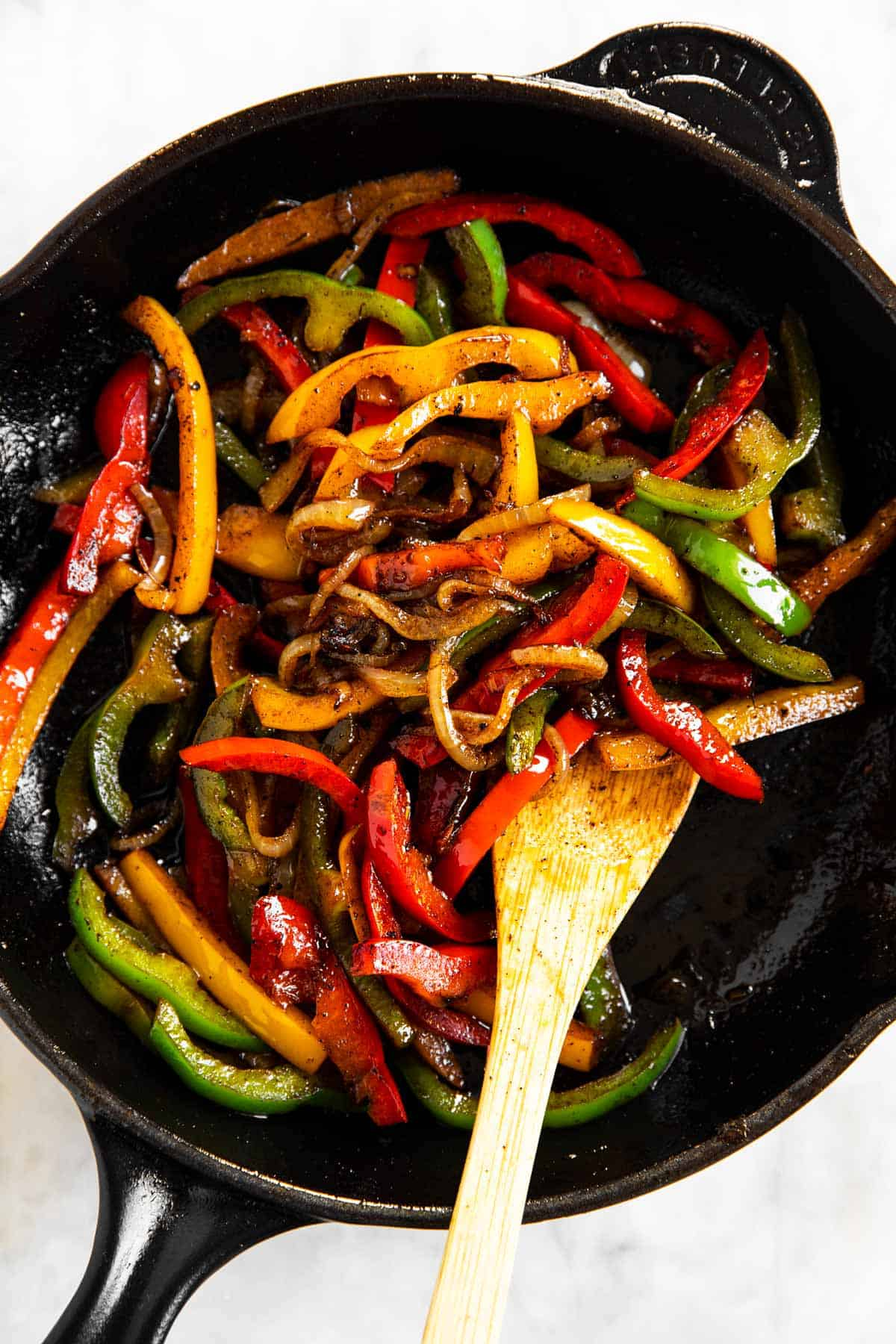cooked onions and peppers in cast iron skillet with wooden spoon