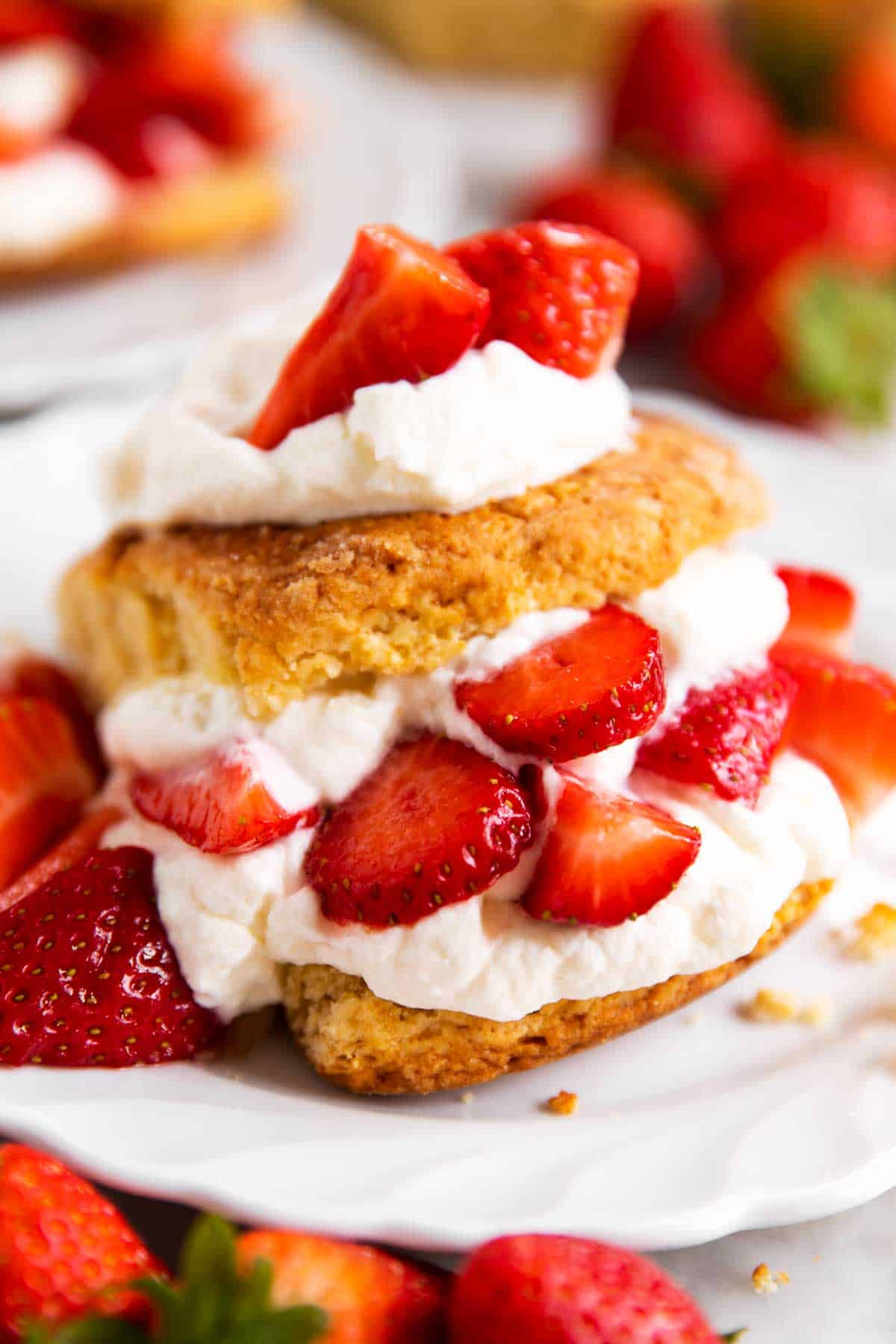 angled view of strawberry shortcake on white plate surrounded by fresh strawberries