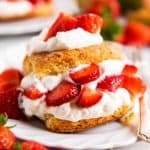 strawberry shortcake on white plate surrounded by fresh strawberries