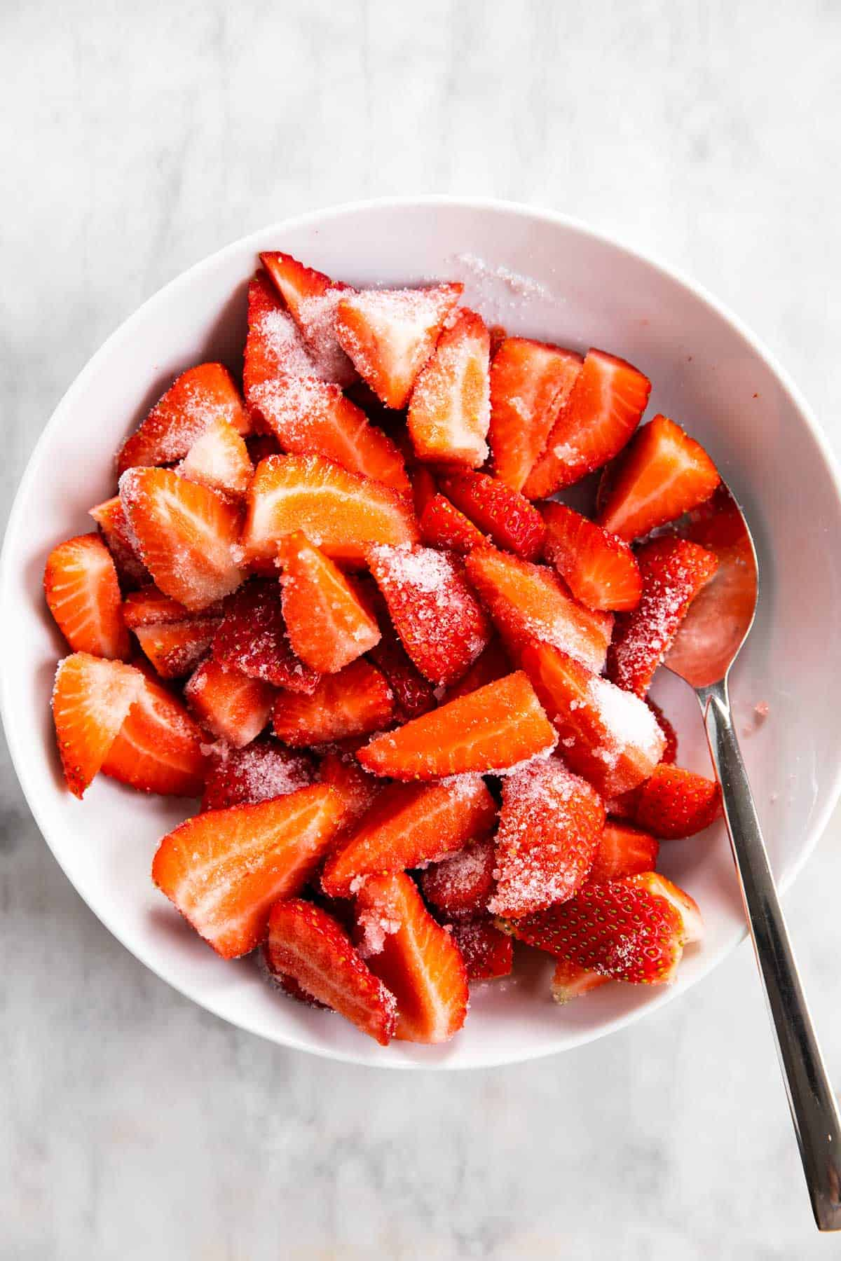 sliced strawberries in white bowl with sugar