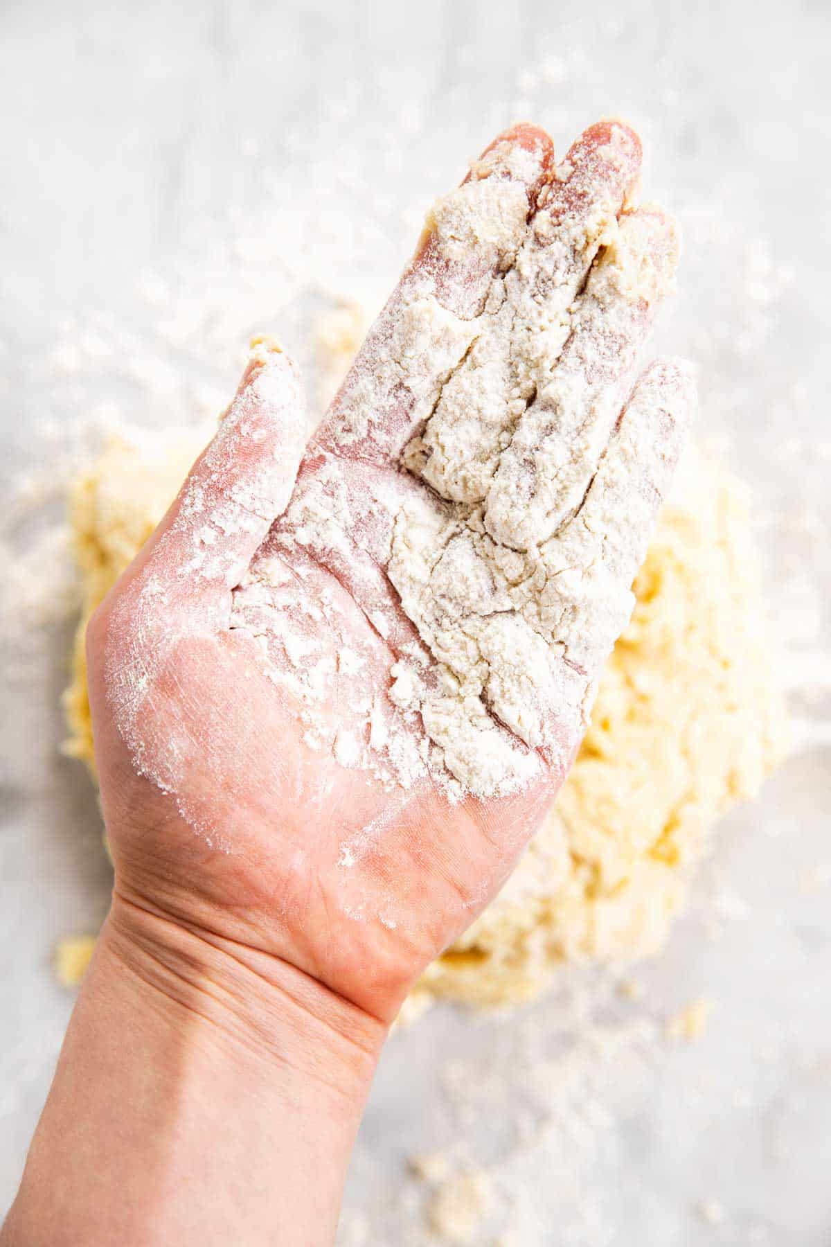 floured hand hovering over biscuit dough