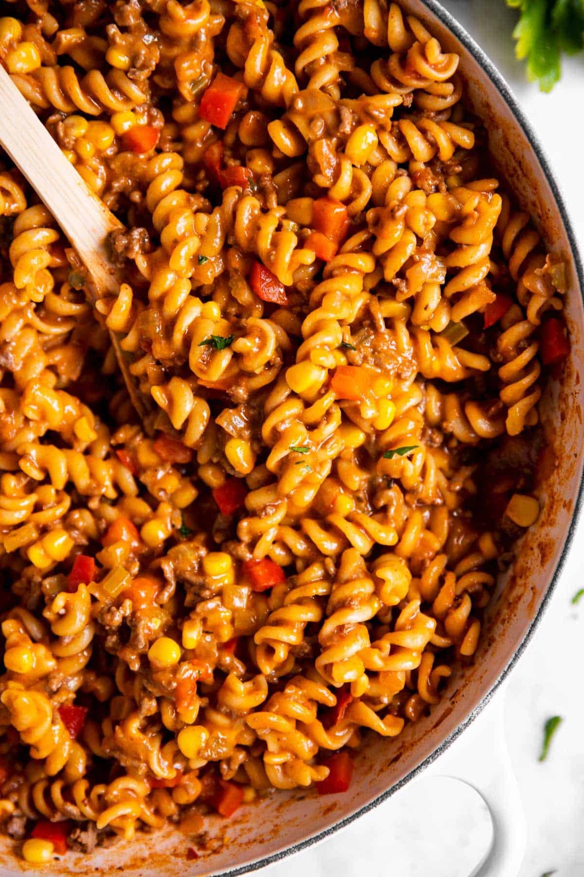 overhead close up of taco pasta in white skillet with wooden spoon