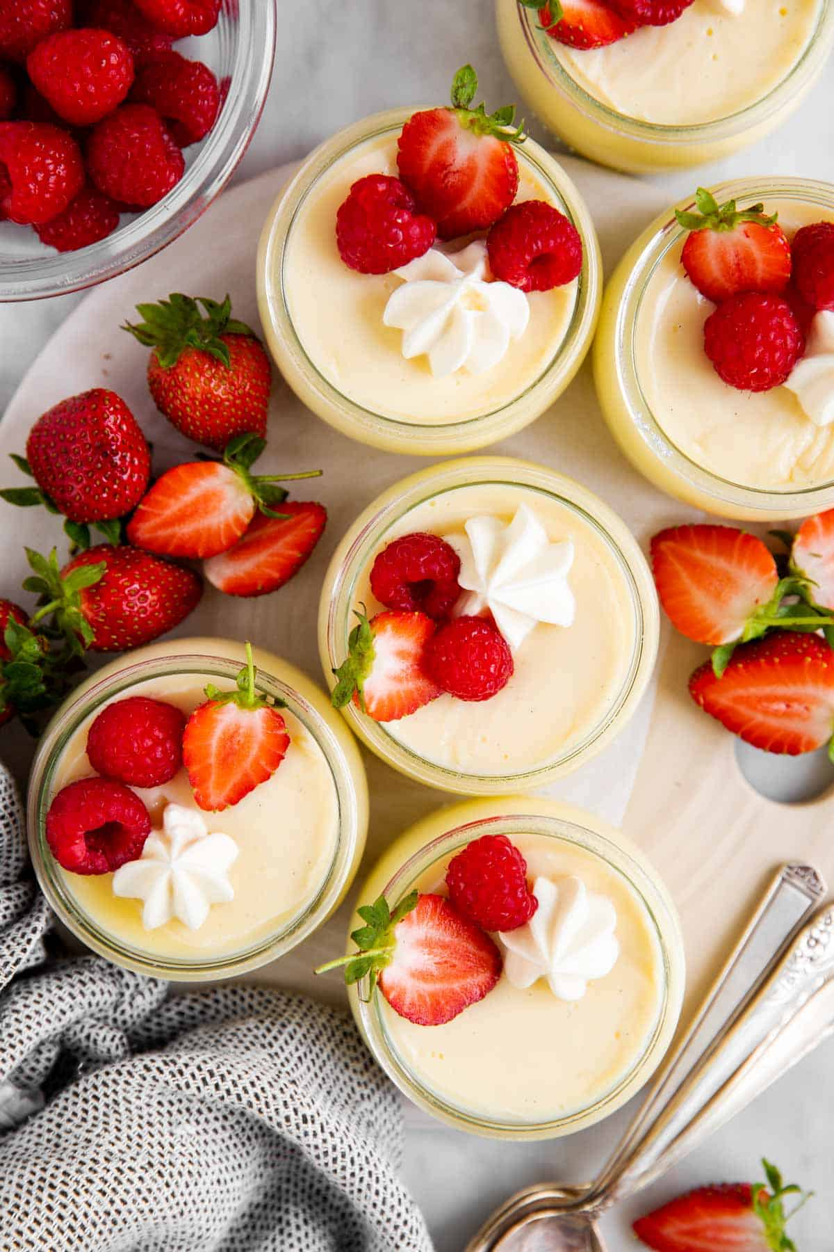six individual vanilla pudding cups on serving platter with fresh berries