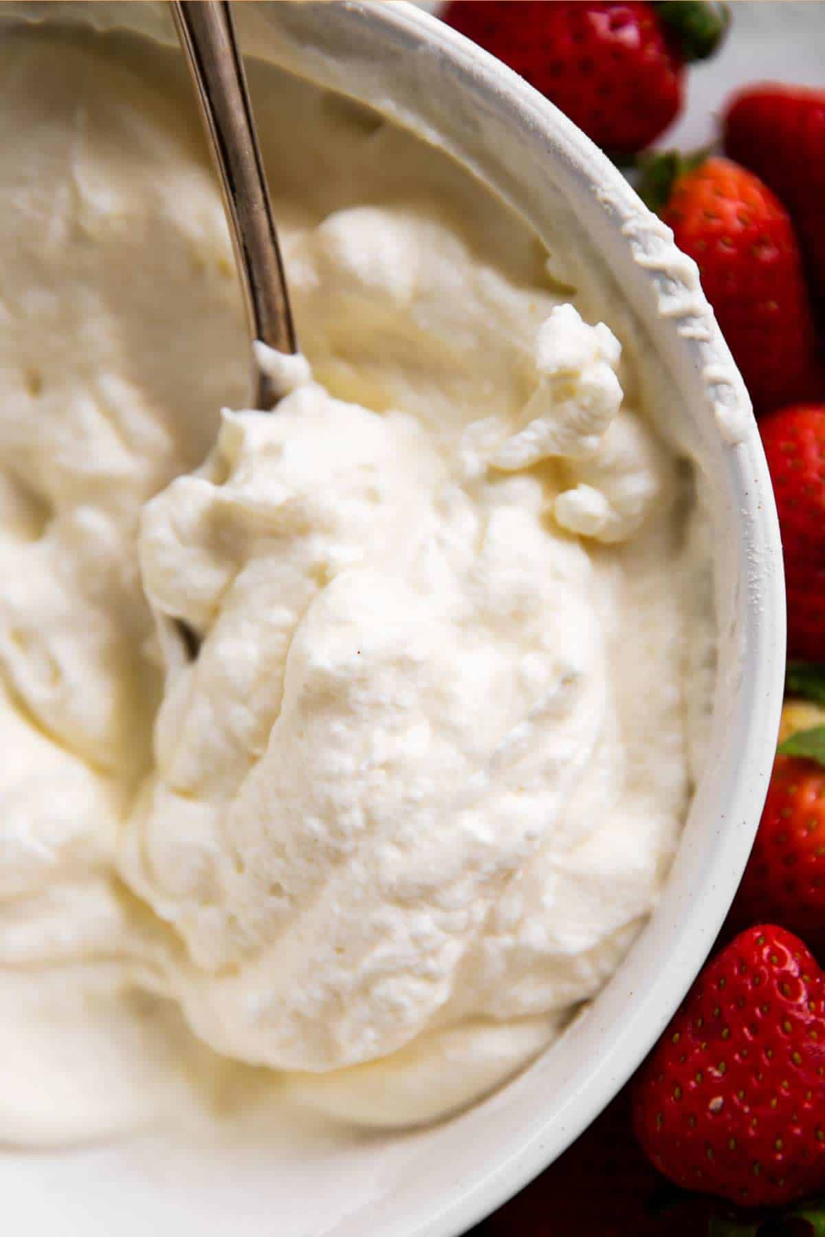 overhead view of whipped cream in white bowl with spoon next to fresh strawberries