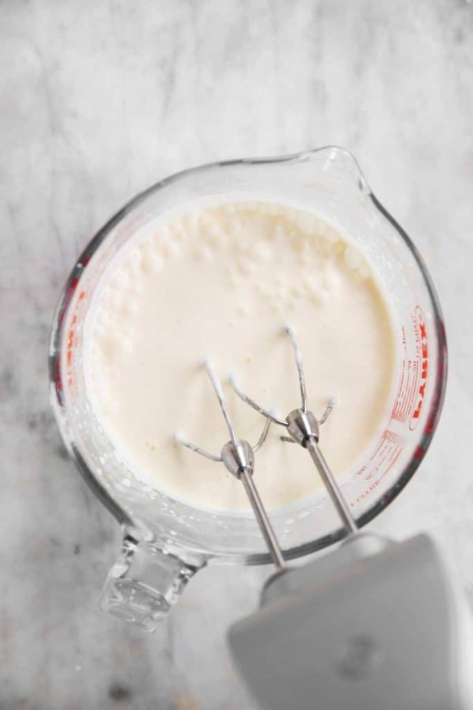 homemade whipped cream in glass measuring jug after one minute of whipping