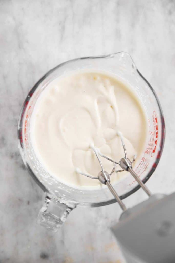 homemade whipped cream in glass measuring jug after two minutes of whipping