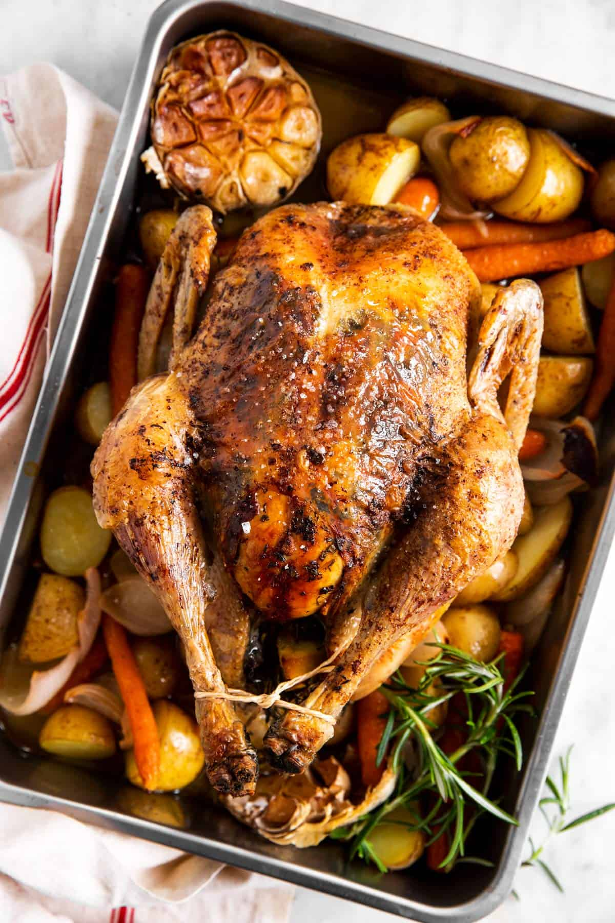 overhead view of whole roasted chicken in roasting pan with carrots and potatoes
