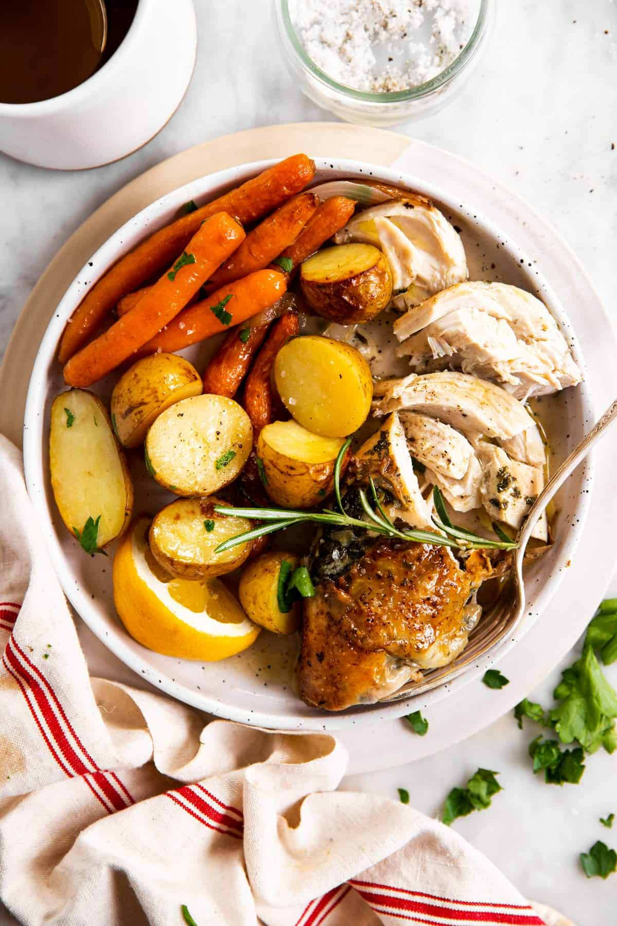 overhead view of carved chicken breast with potatoes and carrots on white plate
