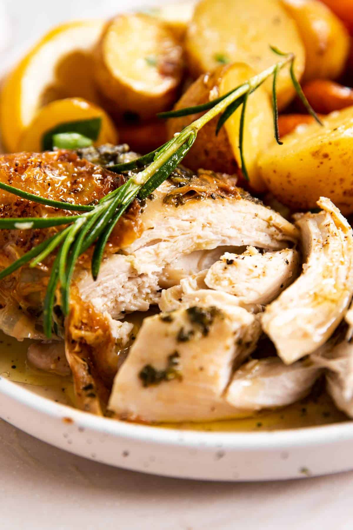 close up view of sliced roasted chicken breast on plate with fresh rosemary, carrots and potatoes