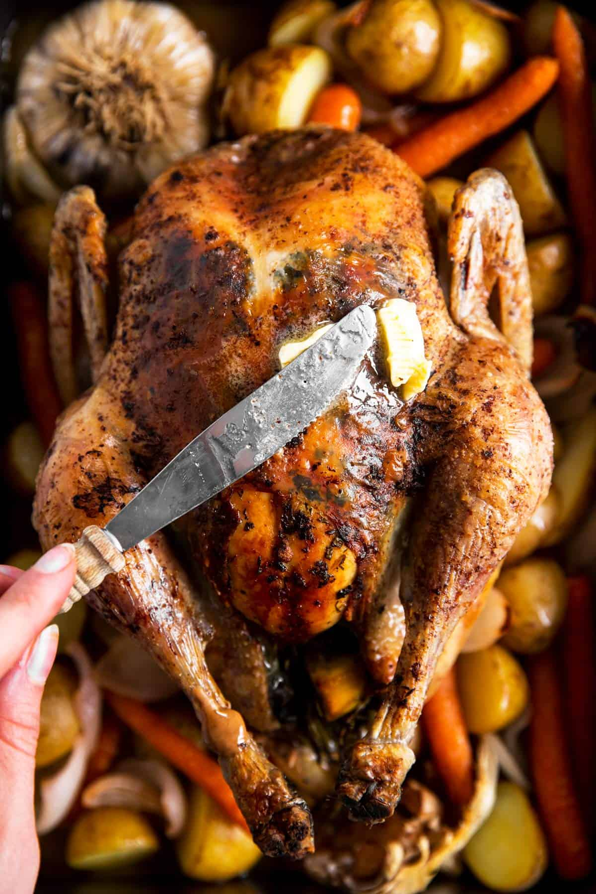 female hand using butter knife to brush butter over roasted chicken