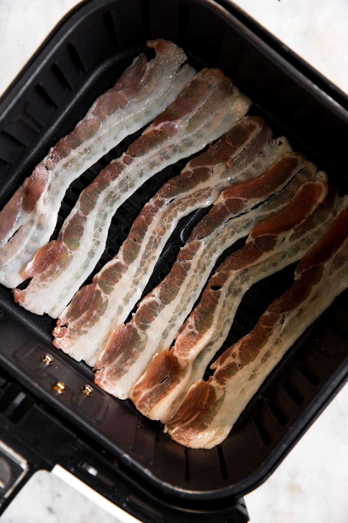 uncooked bacon in air fryer basket