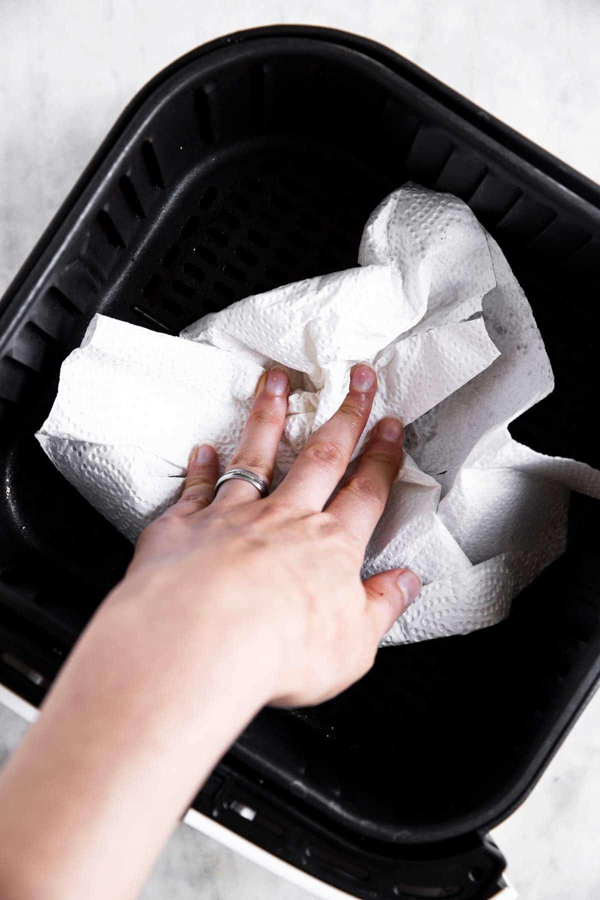 female hand wiping air fryer basket