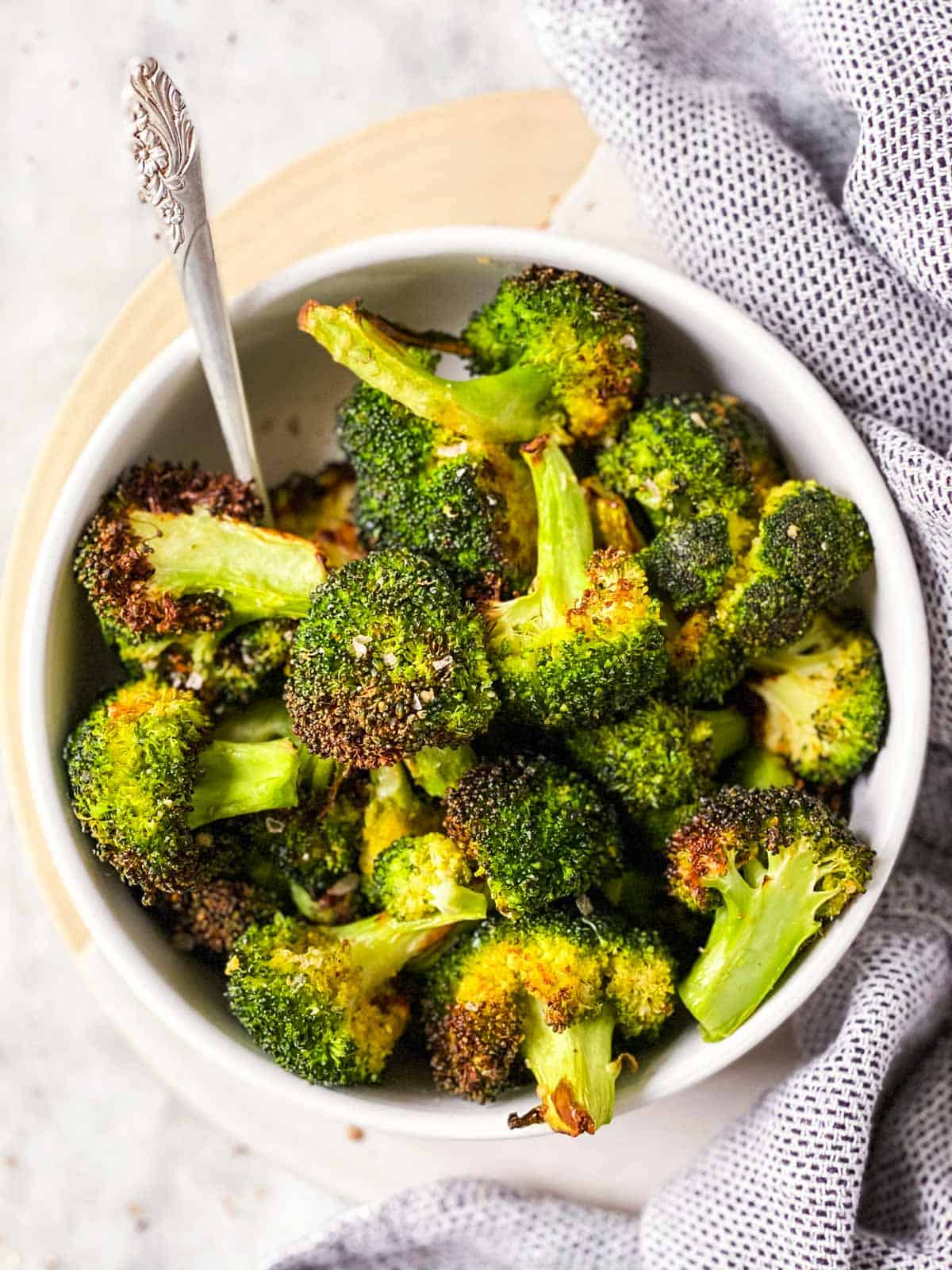 air fried broccoli in white bowl next to cloth napkin