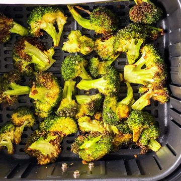 overhead view of roasted broccoli in air fryer basket