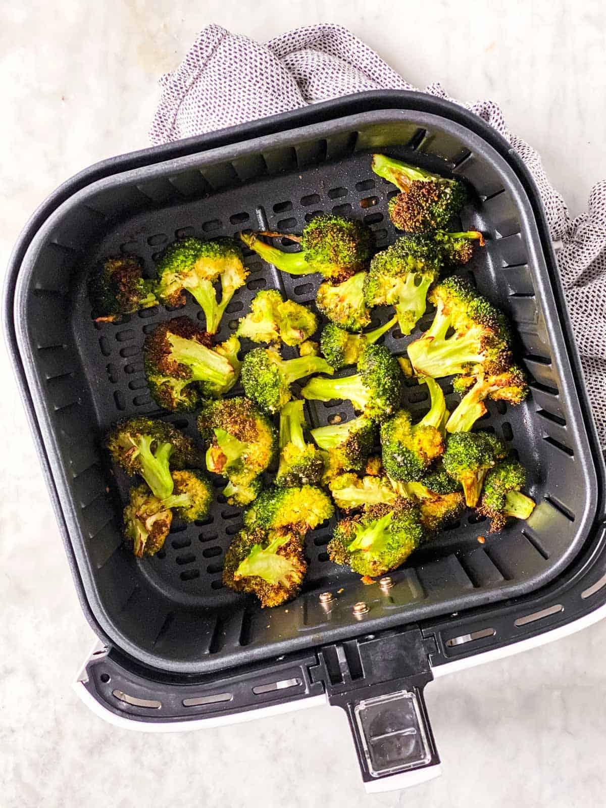 air fryer basket with roasted broccoli florets inside