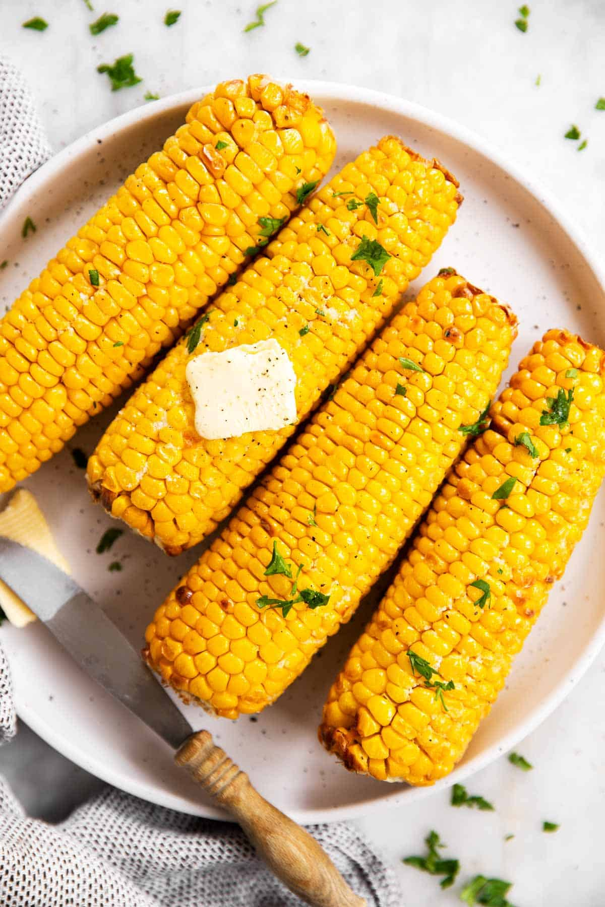 four air fried ears of corn on white plate with butter and parsley
