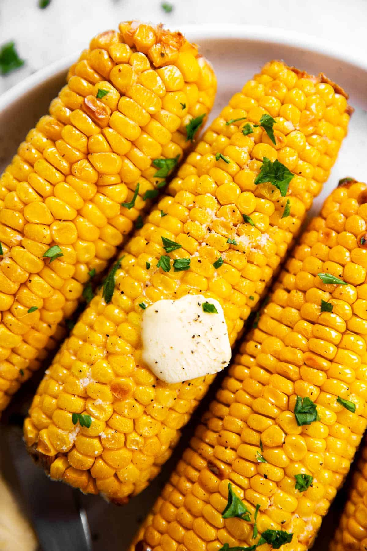 close up photo of air fried corn on the cob on a white plate, with butter and chopped parsley