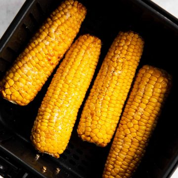 four cooked ears of corn in air fryer basket