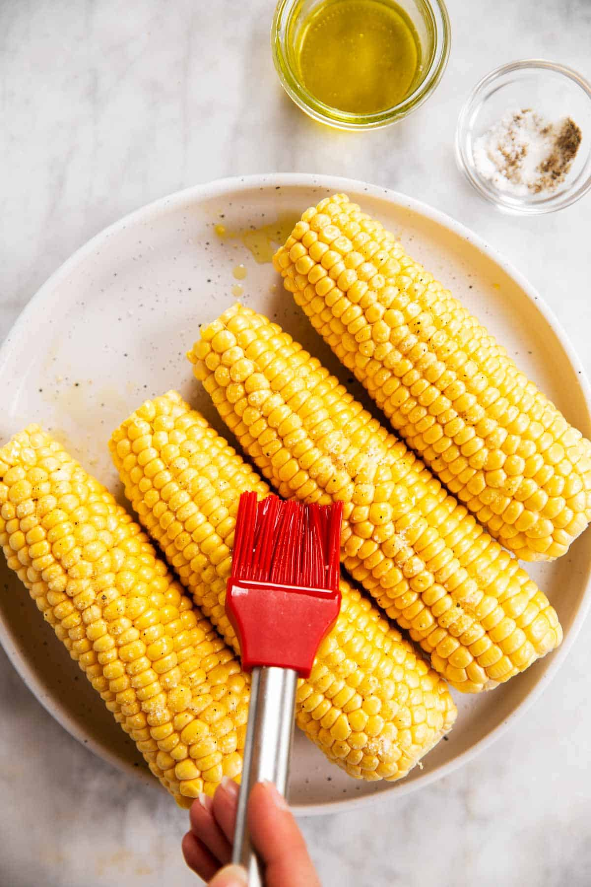 four ears of shucked corn on white plate, female hand brushing one with oil using a red pastry brush