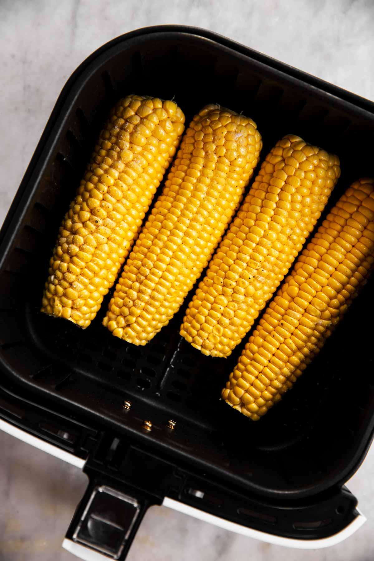 four seasoned ears of corn in air fryer basket