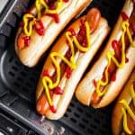 close up photo of hot dogs in air fryer basket with mustard and ketchup