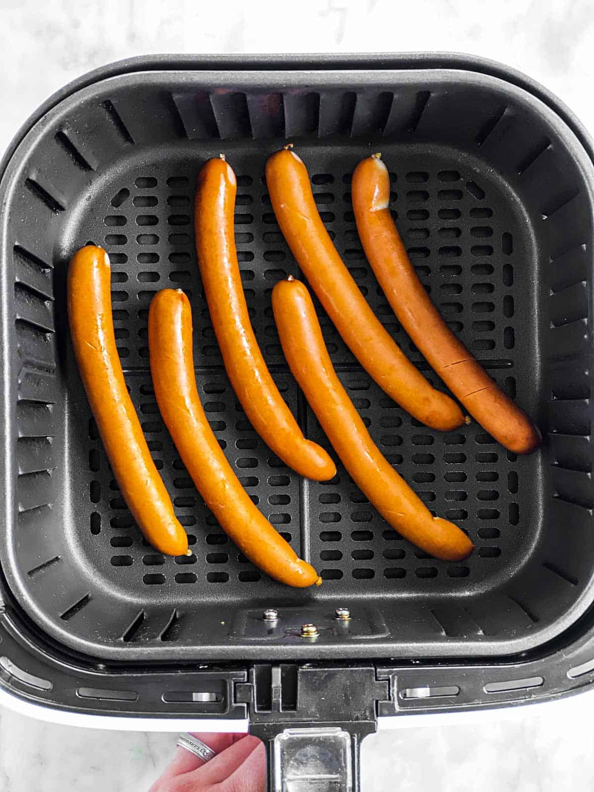 six uncooked hot dogs in air fryer basket