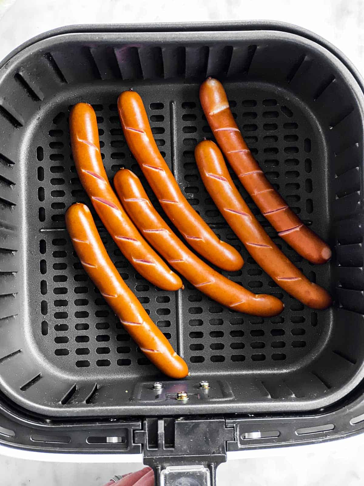 six cooked hot dogs in air fryer basket