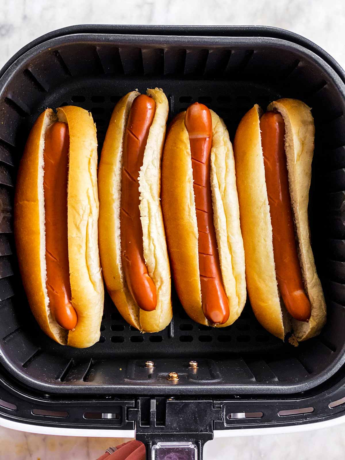four hot dogs in buns in air fryer basket
