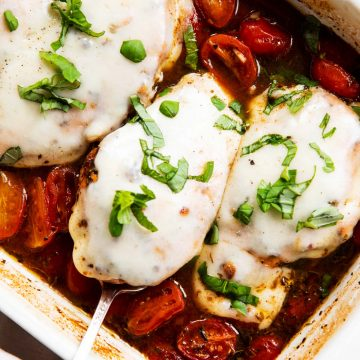 overhead view of baked caprese chicken in white ceramic casserole dish, garnished with fresh basil