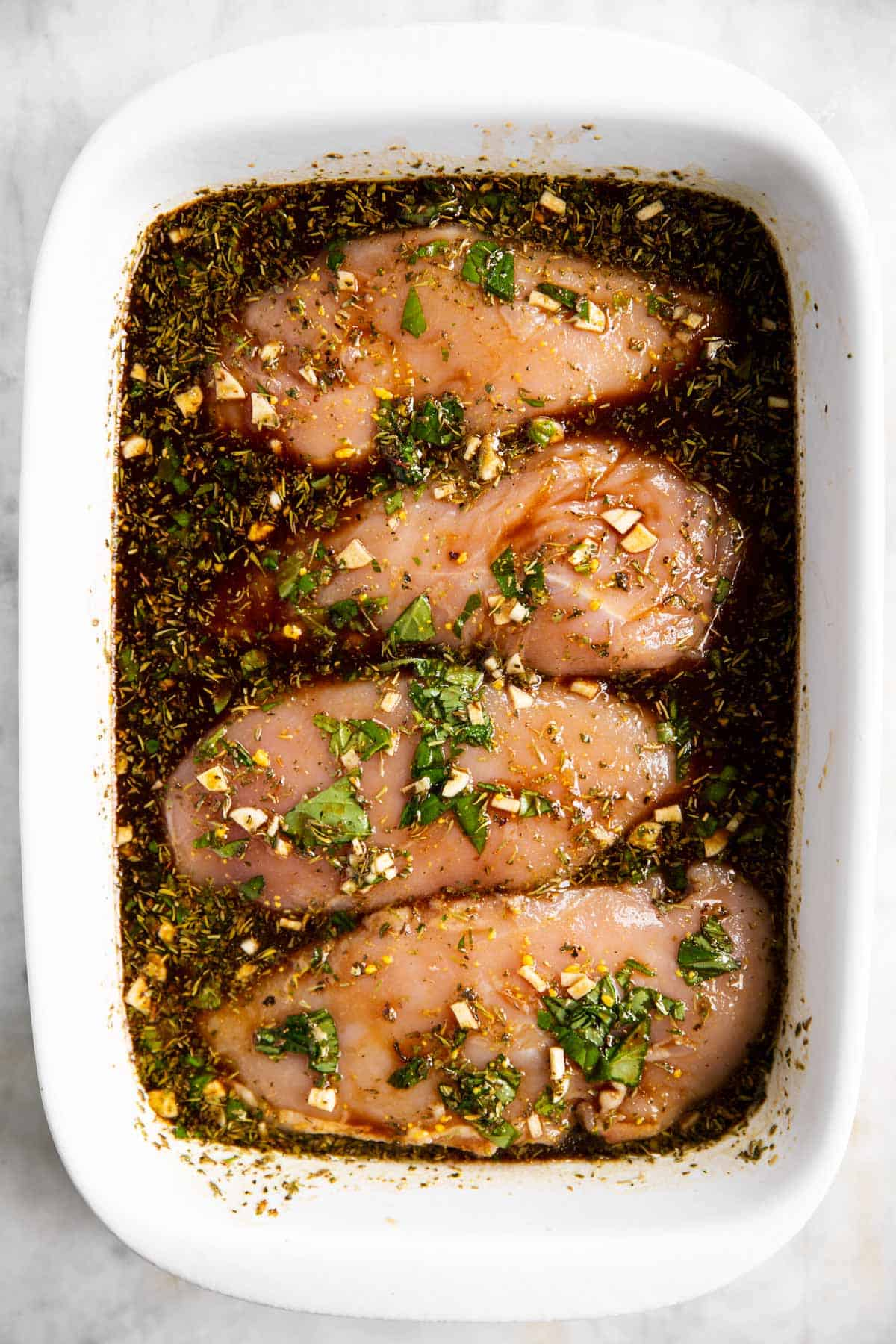 four raw chicken breasts in white casserole dish with balsamic marinade
