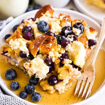 slice of blueberry French toast casserole with maple syrup on white plate
