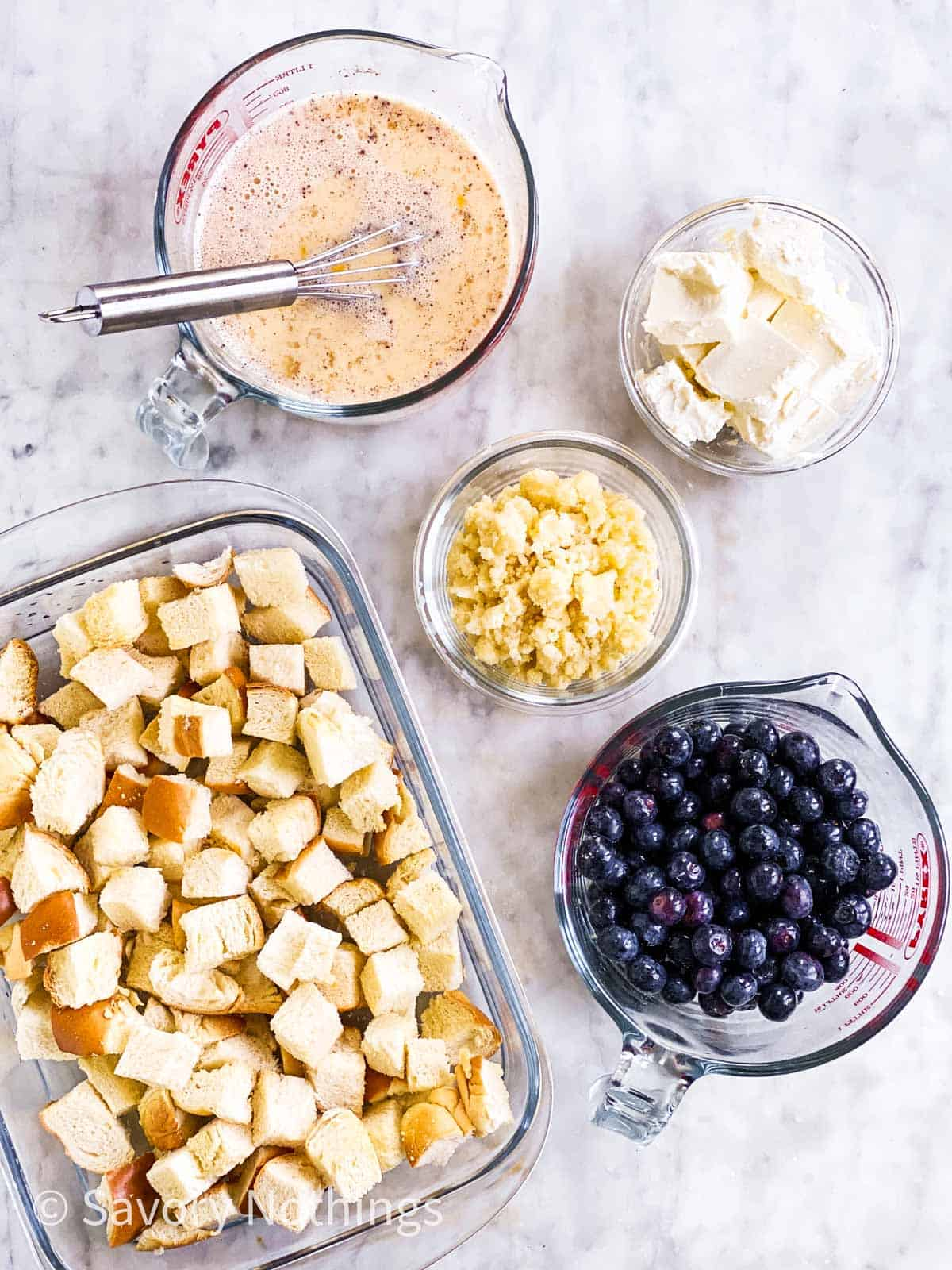 prepared ingredients for a blueberry French toast casserole on a white marble surface