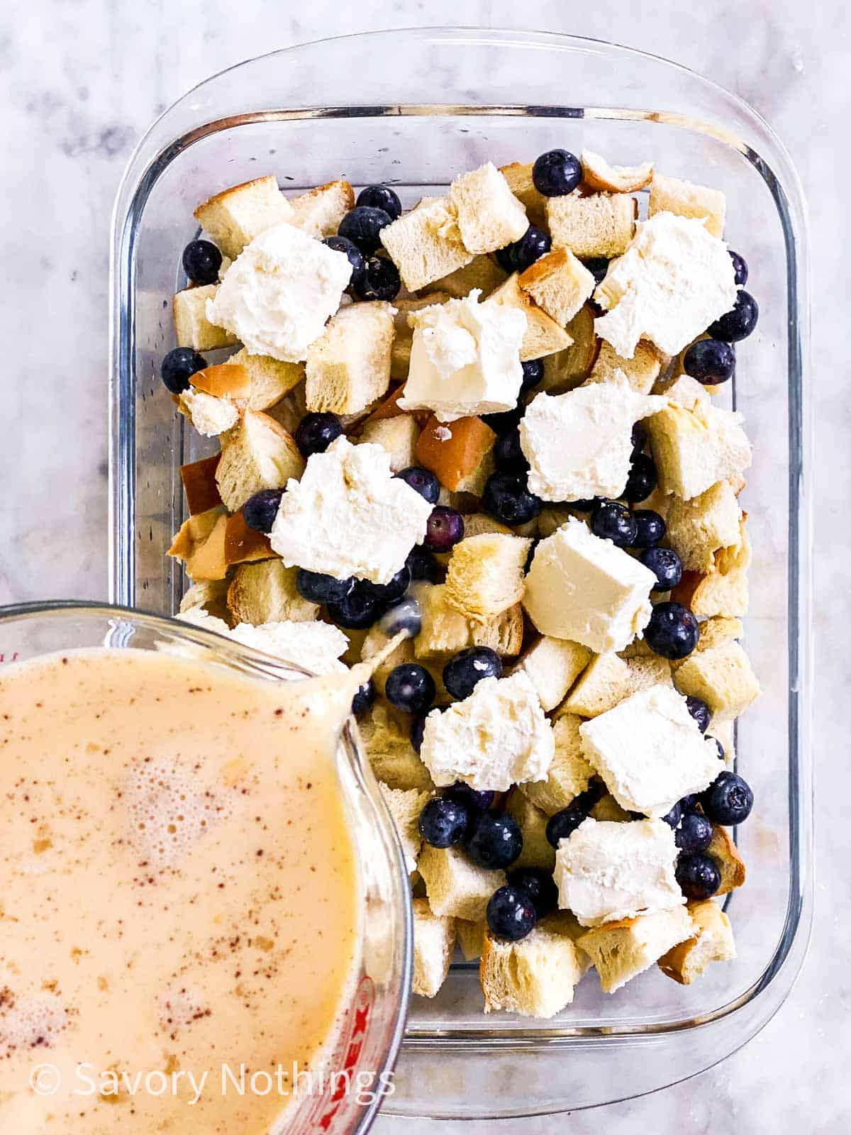 egg and milk mixture pouring over blueberry French toast casserole ingredients in glass dish