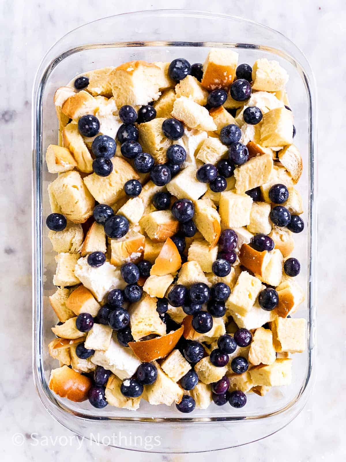 assembled but unbaked blueberry French toast casserole in glass dish sitting on white marble surface
