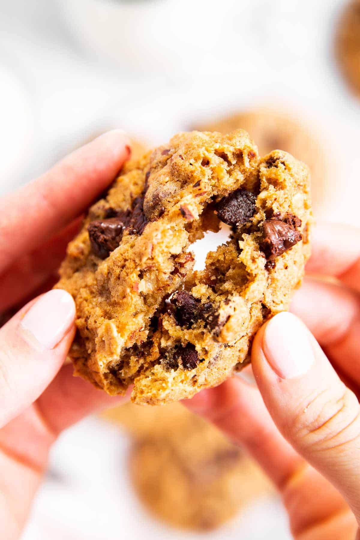 female hands breaking oatmeal chocolate chip cookie in half