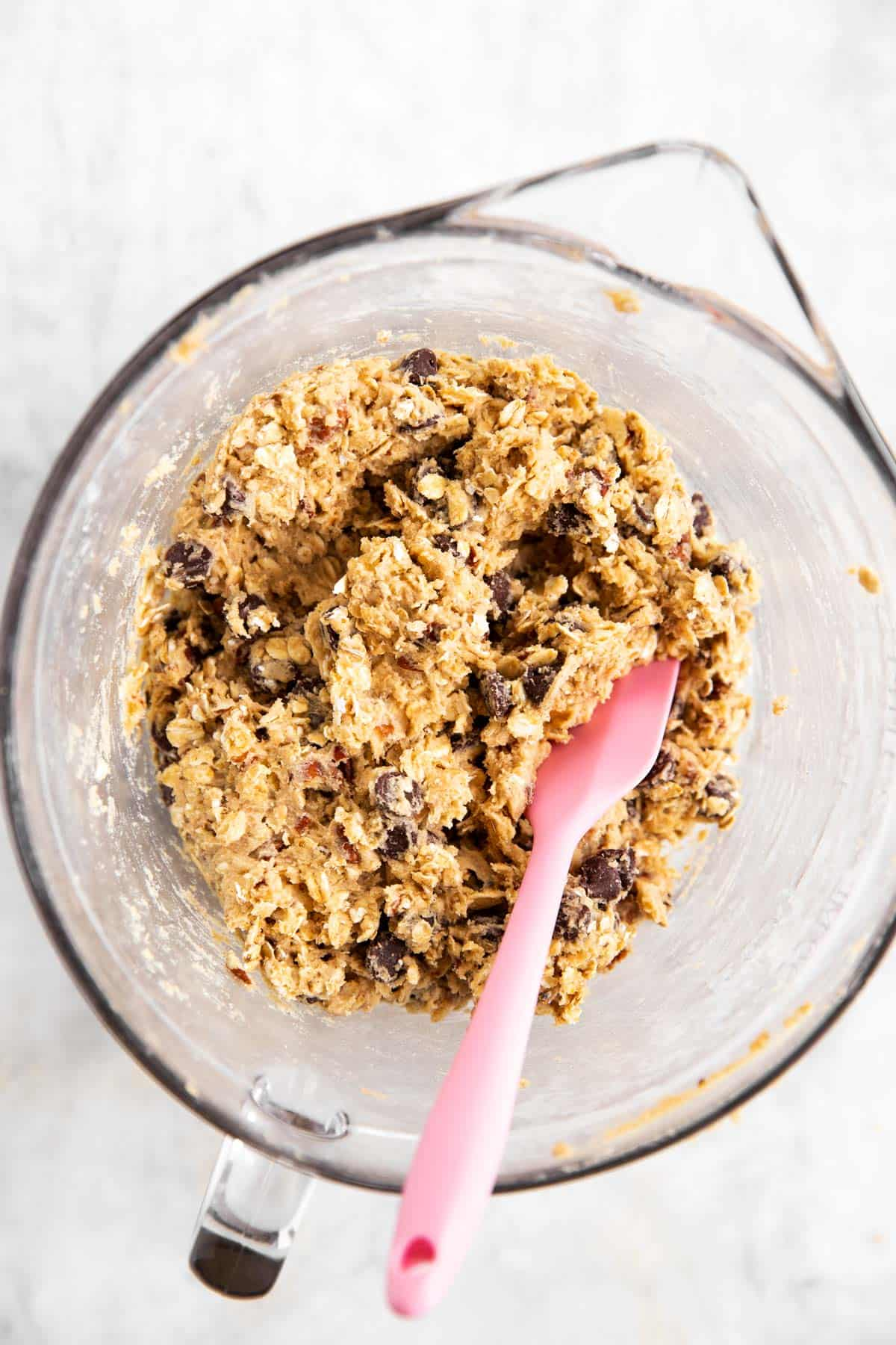 oatmeal chocolate chip cookie dough in glass bowl with pink spatula stuck in