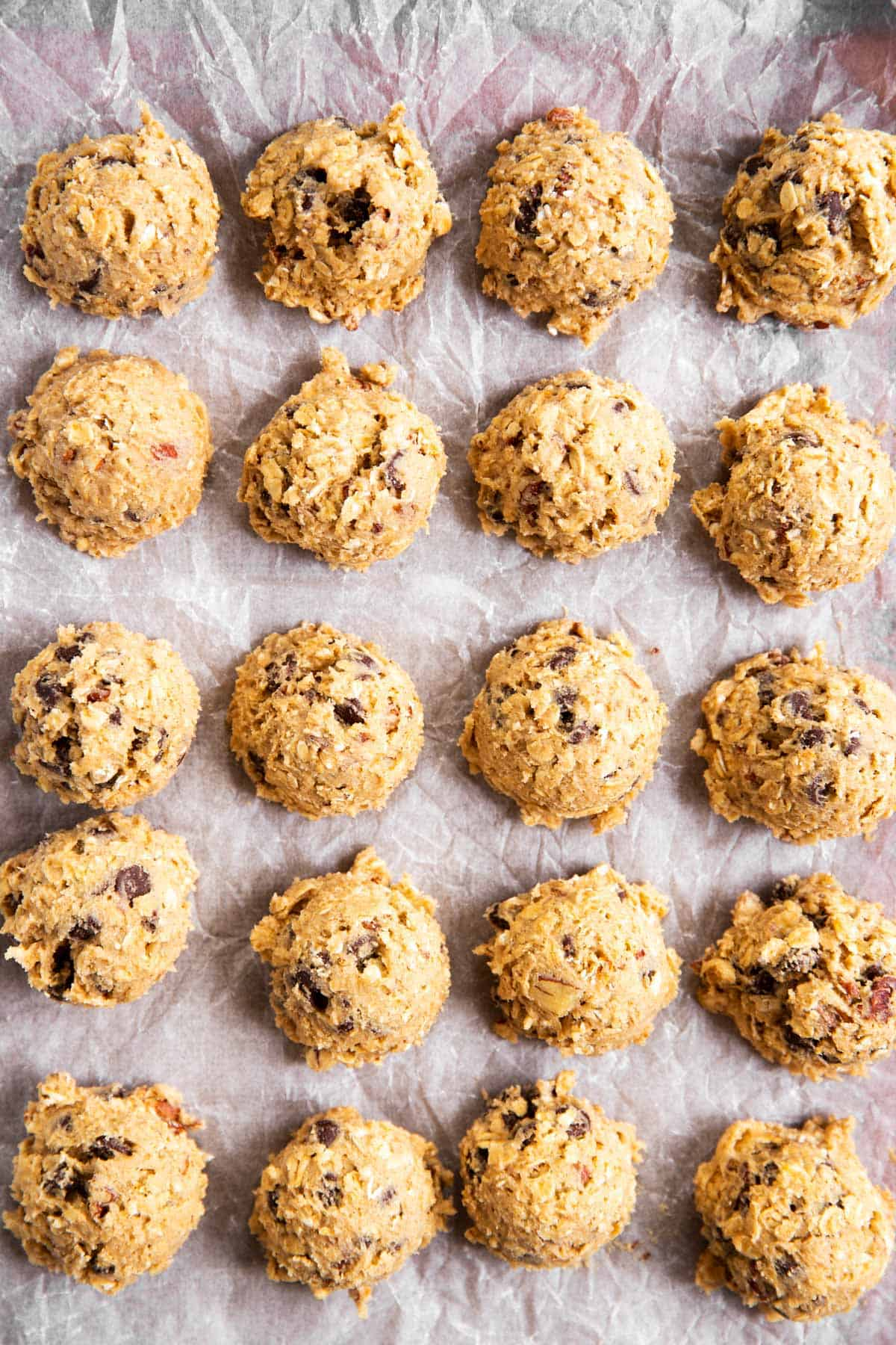 twenty oatmeal chocolate chip cookie dough balls on lined baking sheet