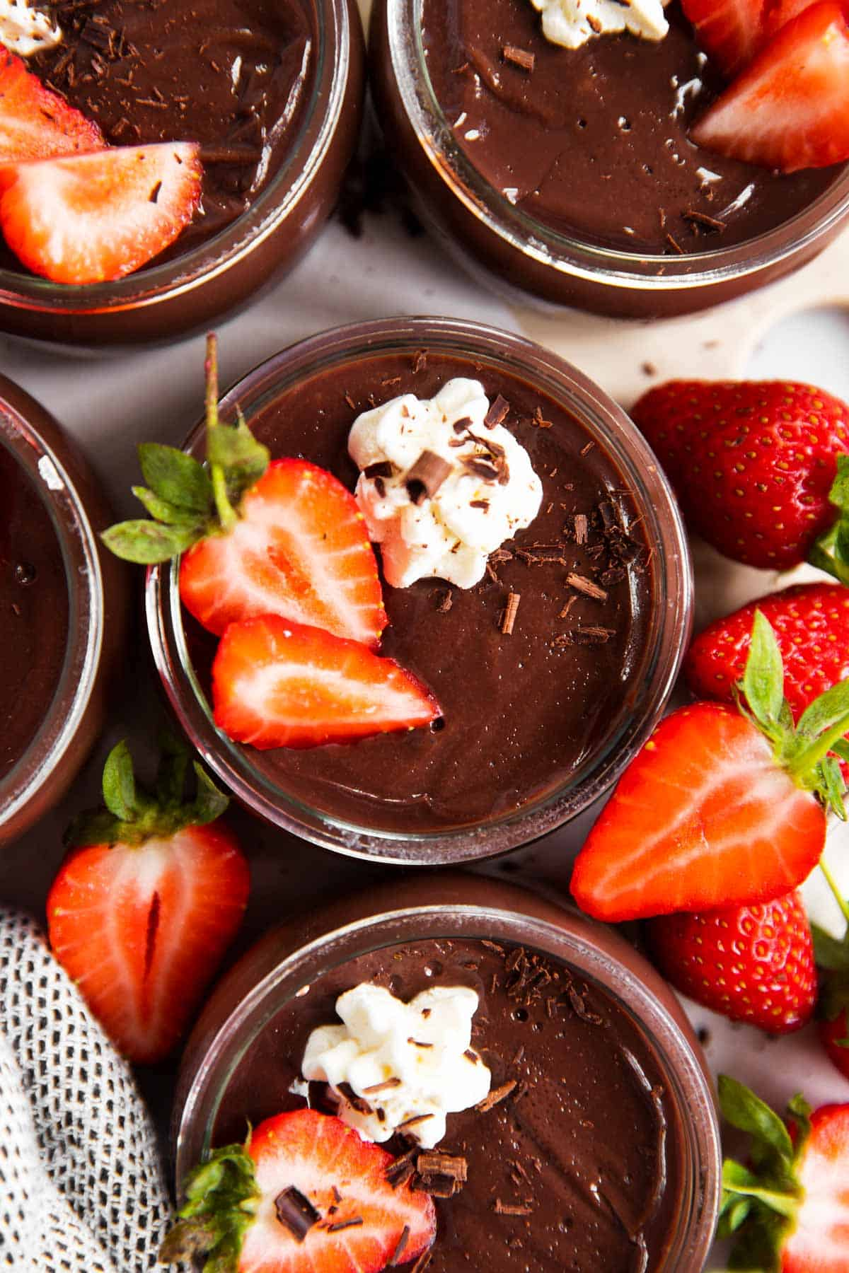 overhead view of several jars with chocolate pudding, garnished with whipped cream and strawberries