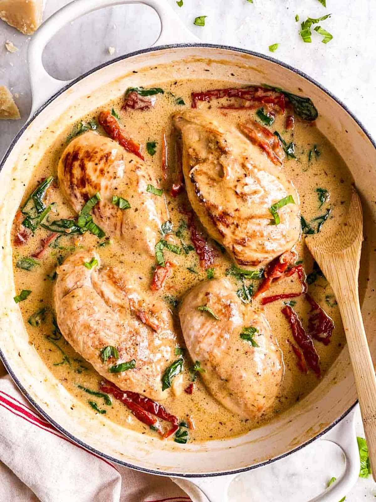 overhead view of tuscan chicken in white cast iron skillet