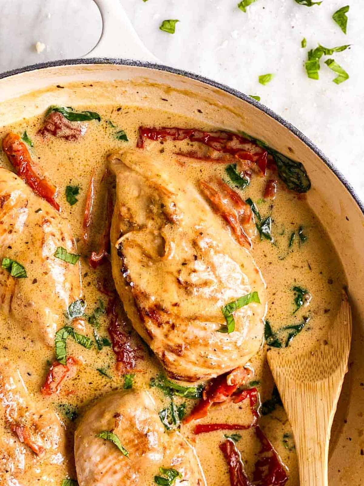 close up photo of chicken breast smothered in creamy tuscan sauce with sun-dried tomatoes and spinach