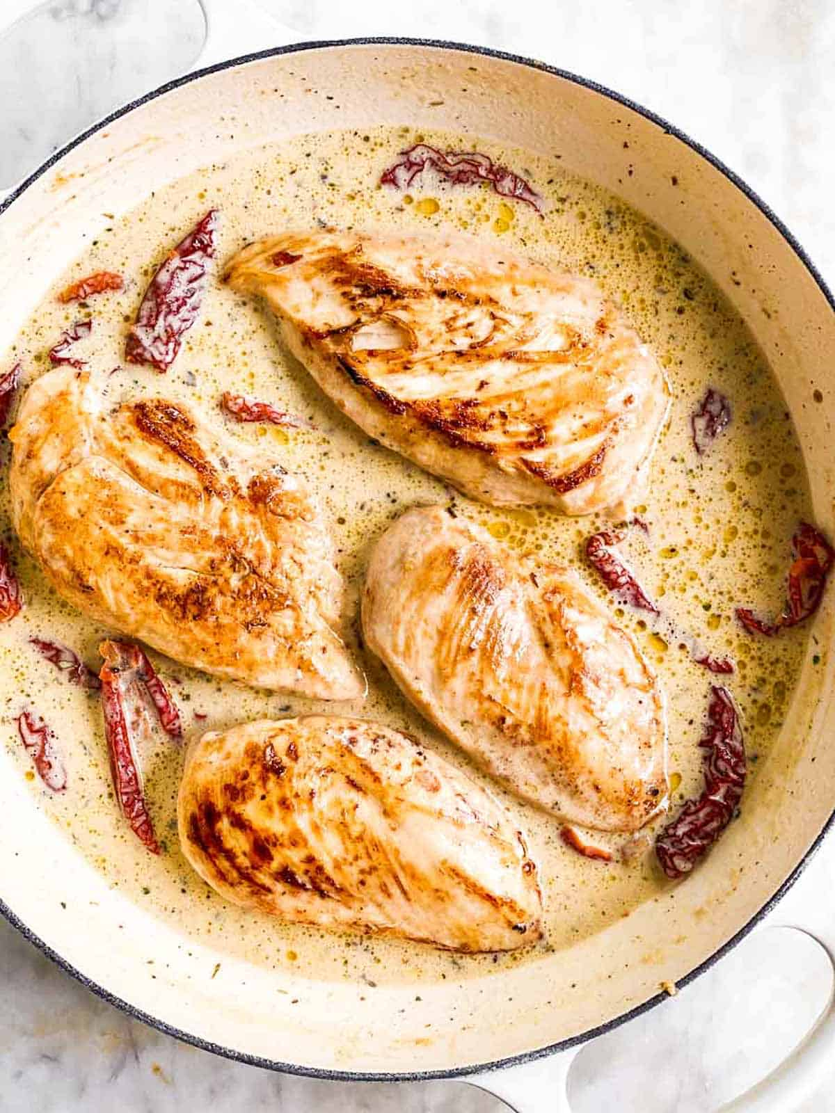 cooked chicken breasts in creamy sauce in white cast iron skillet
