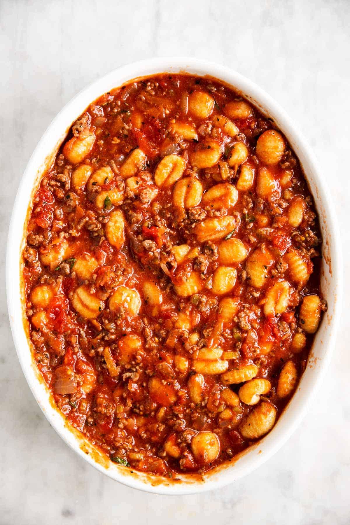 gnocchi, ground beef and tomato sauce mixture in white casserole dish