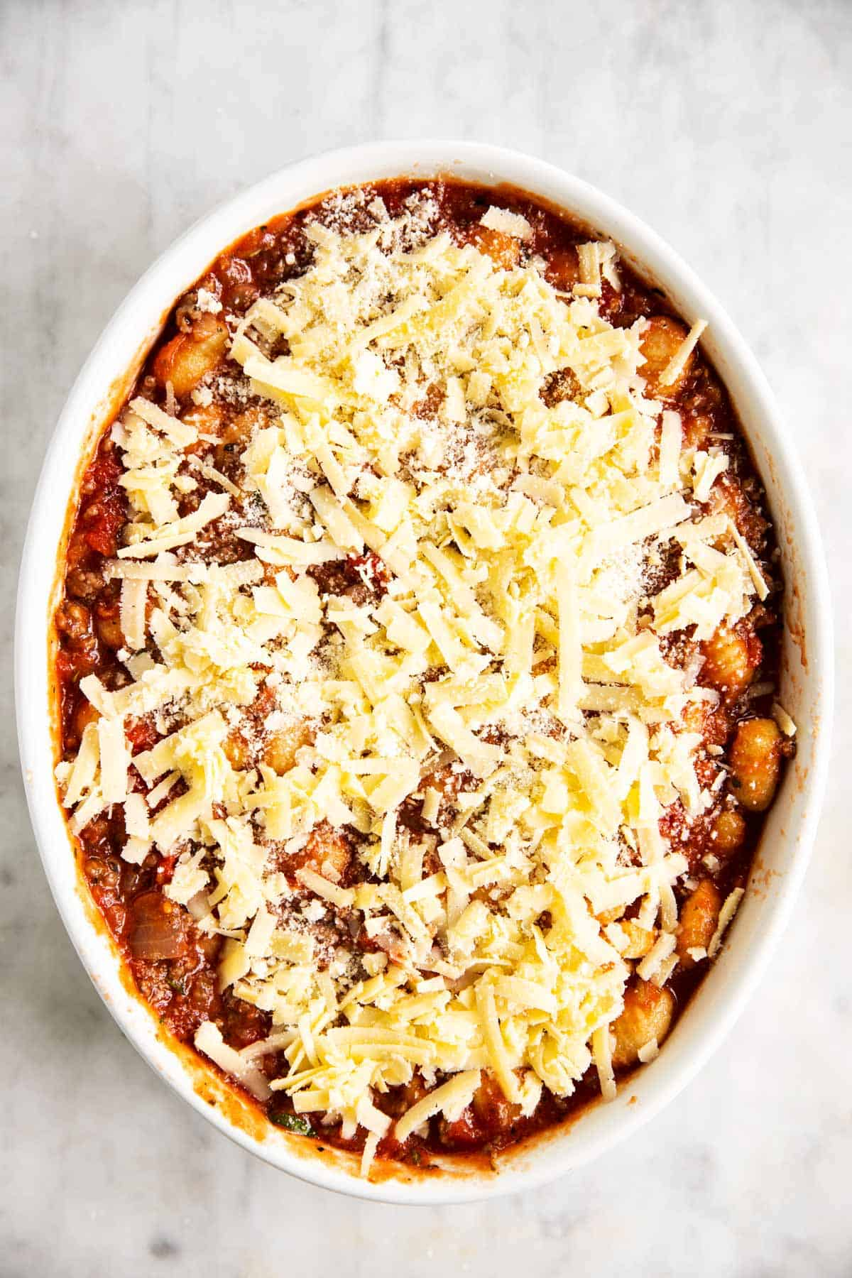 gnocchi, ground beef and tomato sauce mixture in white casserole dish covered with cheese