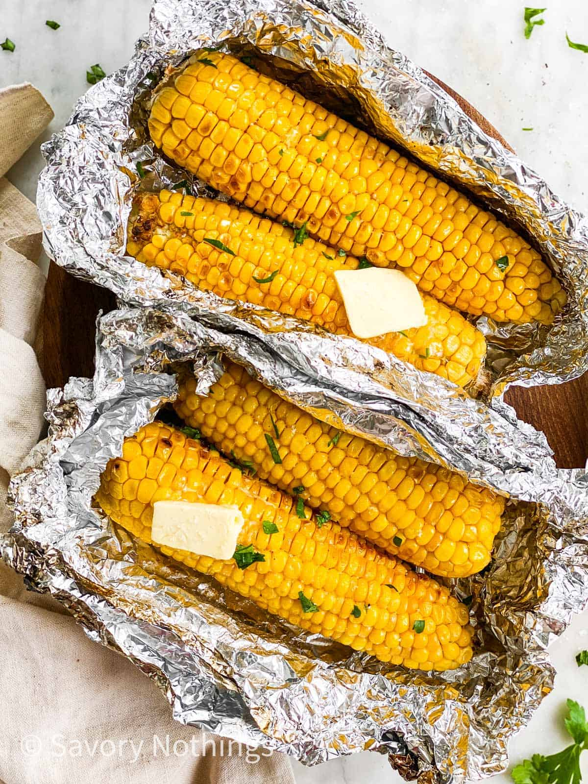 two opened foil packets with two ears of grilled corn each on wooden platter
