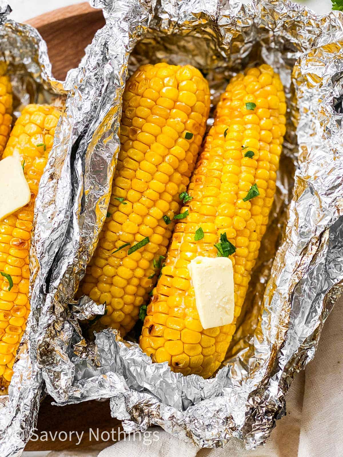 close up photo of two grilled ears of corn in aluminium foil packet with a pat of butter on top